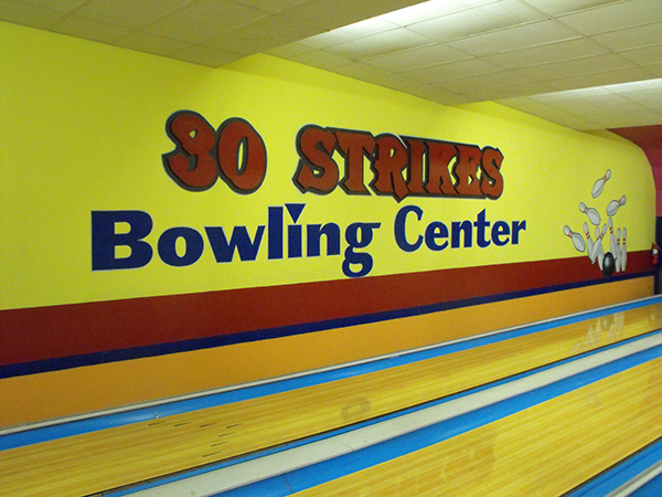 Wall showing 30 strikes bowling center name